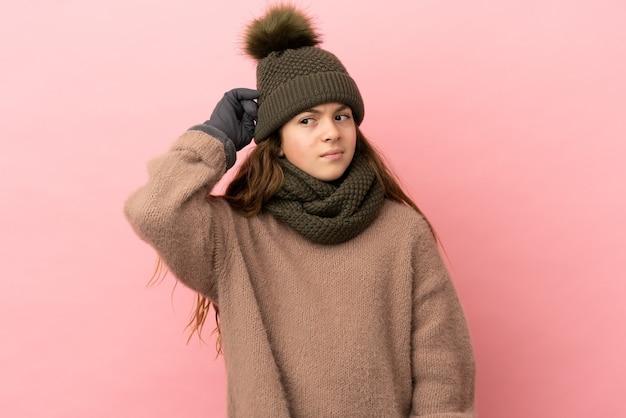 Menina com chapéu de inverno isolada em fundo rosa tendo dúvidas