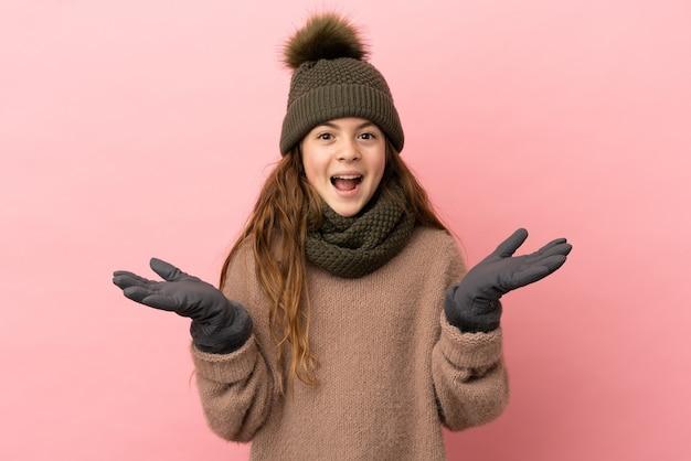 Menina com chapéu de inverno isolada em um fundo rosa com expressão facial de choque