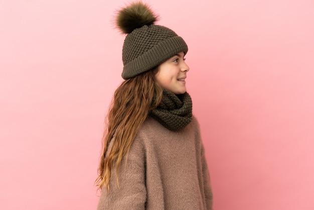 Menina com chapéu de inverno isolada em um fundo rosa olhando de lado