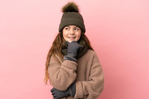 Menina com chapéu de inverno isolada em um fundo rosa olhando para o lado e sorrindo