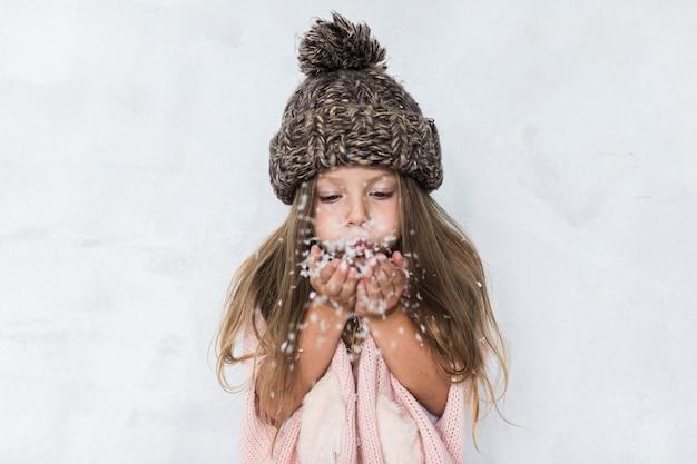Menina com chapéu de inverno soprando neve