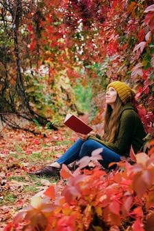 Menina com chapéu de malha amarelo mostarda e suéter de lã verde-pântano sentada entre hera colorida no outono