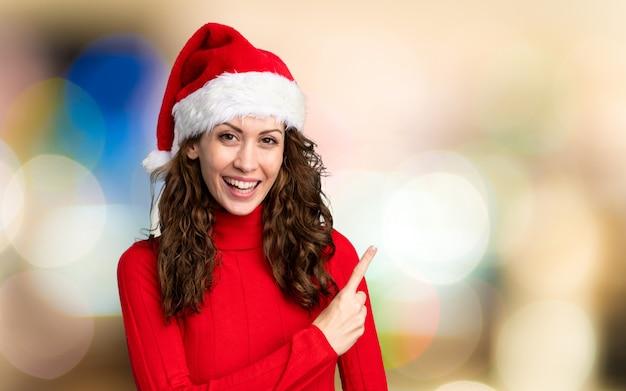 Menina com chapéu de natal, apontando o dedo para o lado, sobre fundo desfocado