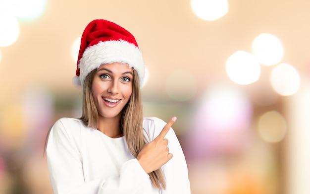 Menina com chapéu de natal, apontando o dedo para o lado sobre parede fora de foco