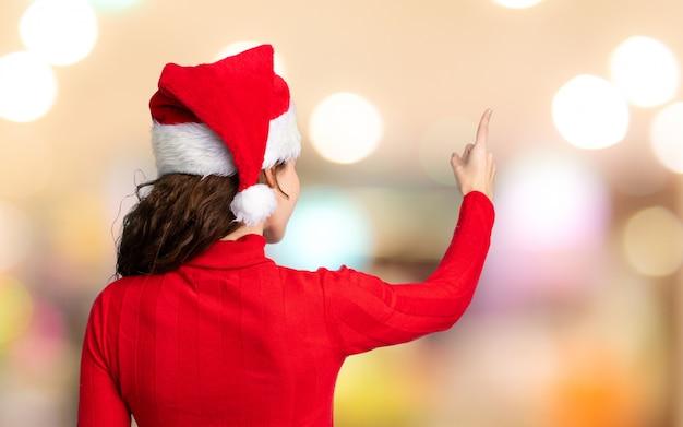 Menina com chapéu de natal apontando para trás com o dedo indicador sobre parede fora de foco