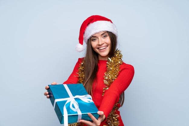 Menina com chapéu de natal e segurando um presente sobre azul isolado