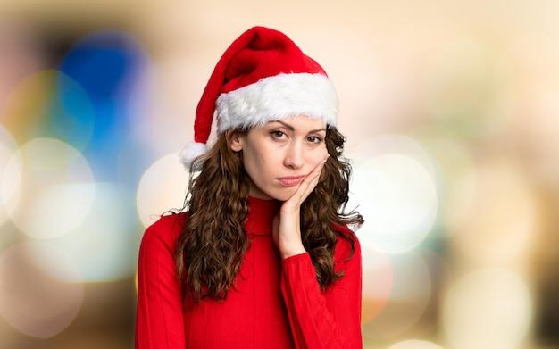 Menina com chapéu de natal infeliz e frustrada por parede fora de foco