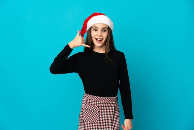 Menina com chapéu de natal isolada na parede azul, fazendo gesto de telefone. ligue-me de volta sinal