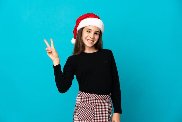 Menina com chapéu de natal isolada na parede azul sorrindo e mostrando sinal de vitória