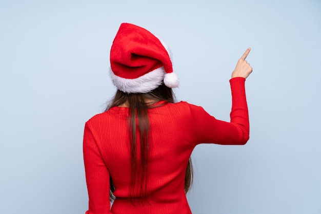 Menina com chapéu de natal isolado azul apontando para trás com o dedo indicador