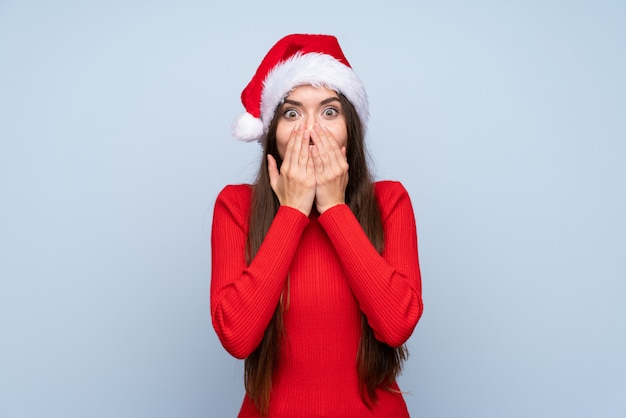 Menina com chapéu de natal isolado azul com expressão facial de surpresa