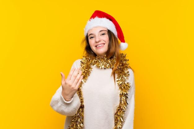 Menina com chapéu de natal isolado muro amarelo convidando para vir