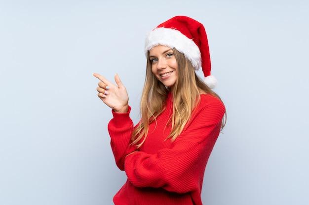 Menina com chapéu de natal isolado parede azul apontando o dedo para o lado