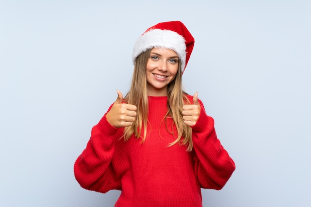 Menina com chapéu de natal isolado parede azul dando um polegar para cima gesto