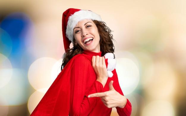 Menina com chapéu de natal segurando uma sacola cheia de presentes na parede fora de foco