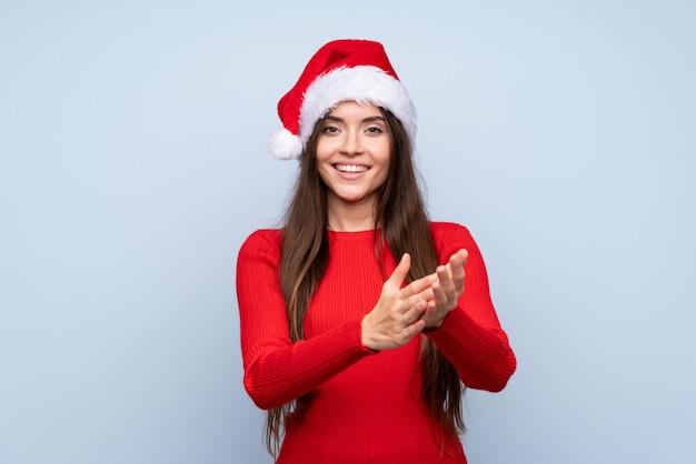 Menina com chapéu de natal sobre aplaudindo azul isolado