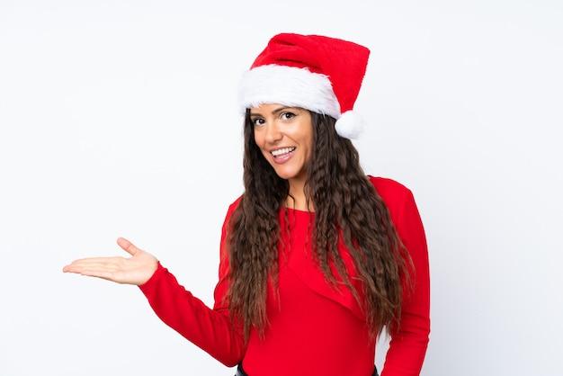 Menina com chapéu de natal sobre fundo branco isolado, segurando copyspace imaginário na palma da mão