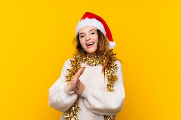 Menina com chapéu de natal sobre parede amarela isolada aplaudindo