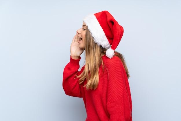 Menina com chapéu de natal sobre parede azul isolada, gritando com a boca aberta