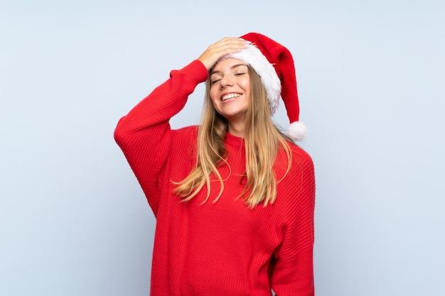Menina com chapéu de natal sobre parede azul isolada rindo
