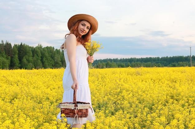 Menina com chapéu de palha em campo de flores amarelas desabrochando