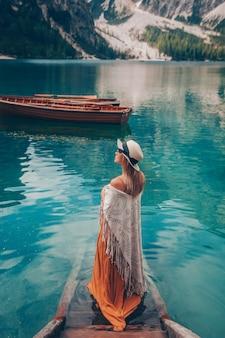 Menina com chapéu de palha no lago turquesa com barcos de madeira nas montanhas.