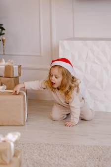Menina com chapéu de papai noel com presente de natal debaixo da árvore de natal. garoto com presente de natal em casa.