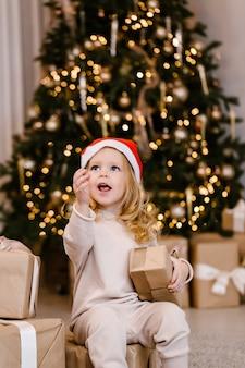 Menina com chapéu de papai noel com presente de natal no fundo da árvore de natal. garoto com presente de natal em casa.