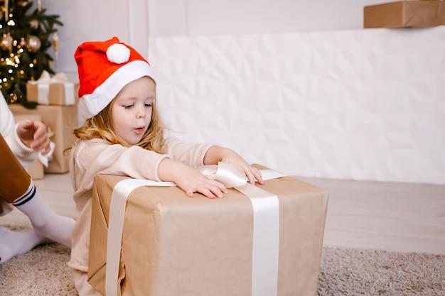 Menina com chapéu de papai noel com presente de natal no fundo da árvore de natal.