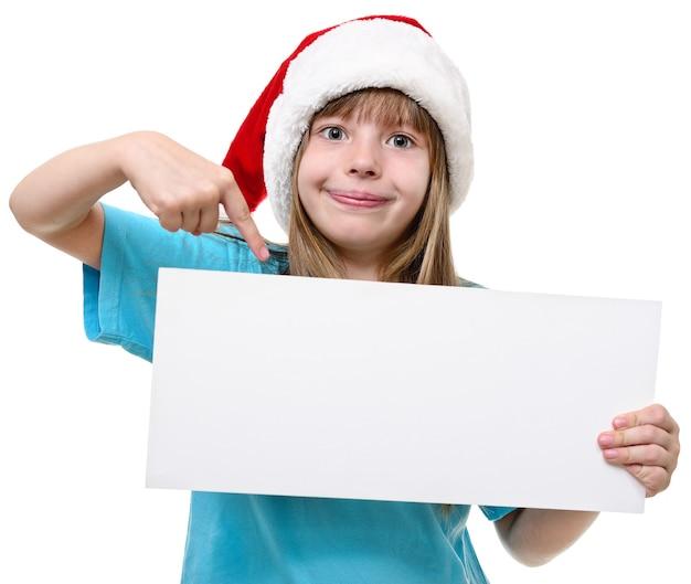 Menina com chapéu de papai noel com quadro branco isolado no branco.