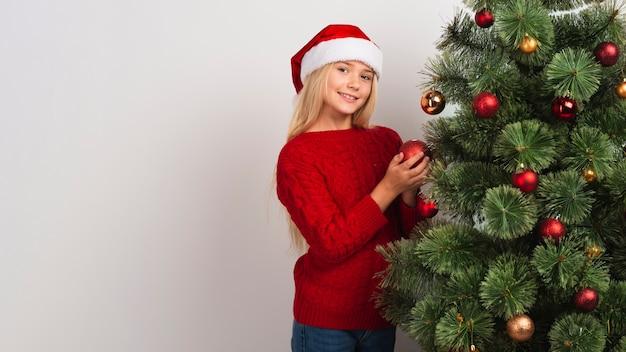 Menina com chapéu de papai noel, decorar a árvore