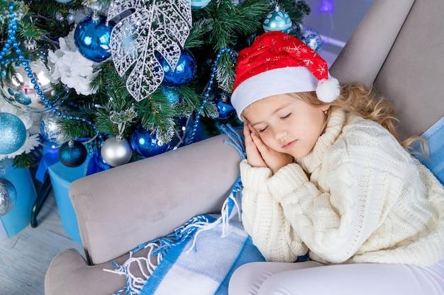 Menina com chapéu de papai noel dormindo perto da árvore de natal
