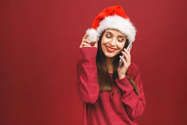 Menina com chapéu de papai noel e celular na mão