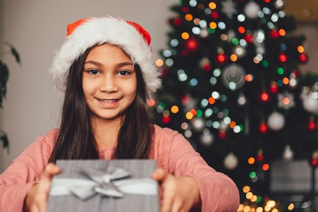 Menina com chapéu de papai noel segurando o presente de natal