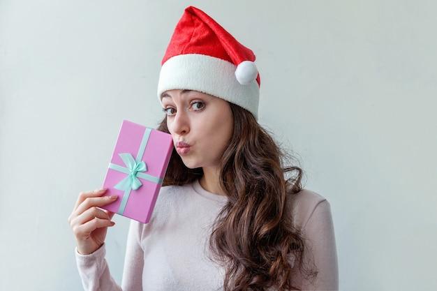 Menina com chapéu de papai noel segurando uma caixa de presente rosa isolada no branco