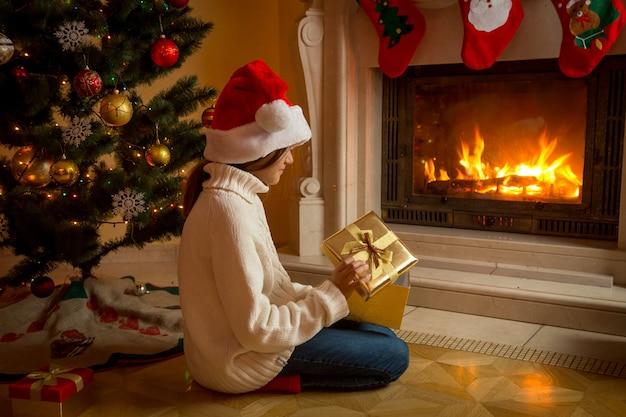 Menina com chapéu de papai noel sentada com caixa de presente de natal na lareira e olhando para o fogo