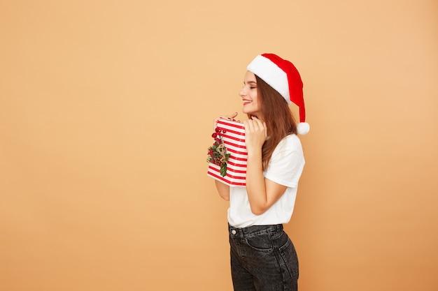 Menina com chapéu de papai noel vestida de jeans e camiseta branca tem um presente de natal nas mãos sobre o fundo bege no estúdio.