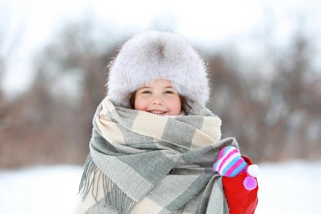 Menina com chapéu de pele e estola em parque de inverno ao ar livre