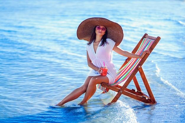 Menina com chapéu de sol e túnica sentada na cadeira de praia à beira-mar enquanto dá coquetéis de férias de verão