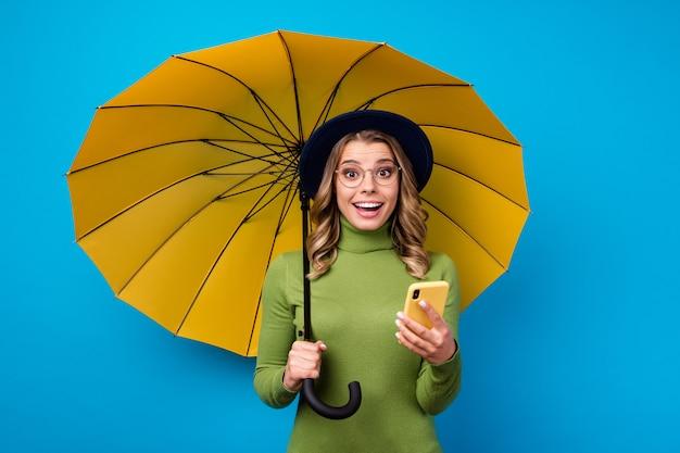 Menina com chapéu e óculos segurando guarda-chuva e telefone