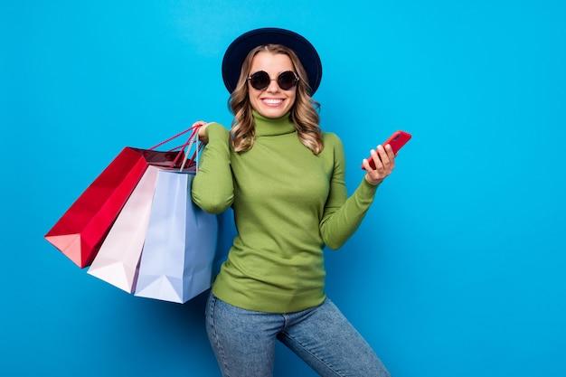 Menina com chapéu e óculos segurando sacolas e telefone