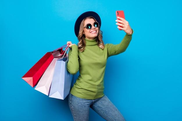 Menina com chapéu e óculos segurando sacolas e tirando selfie