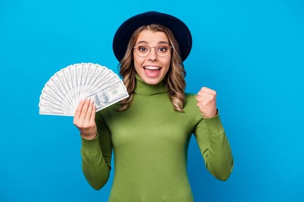 Menina com chapéu e óculos segurando um leque de dinheiro