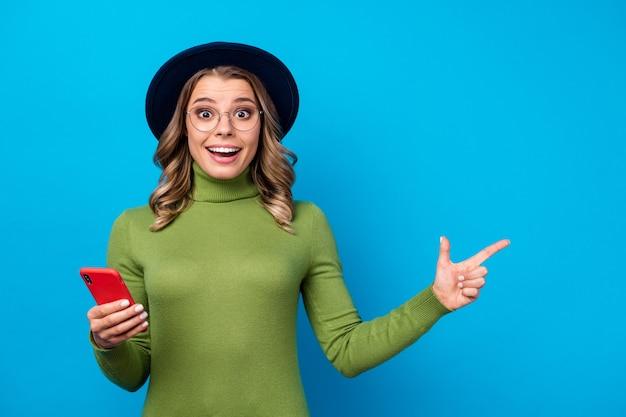 Menina com chapéu e óculos segurando um telefone