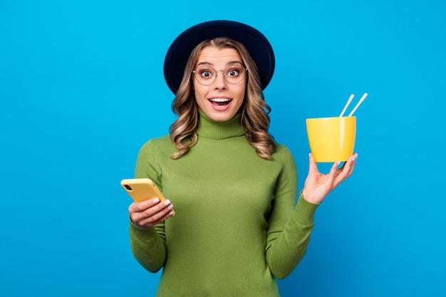 Menina com chapéu e óculos segurando uma tigela e um telefone
