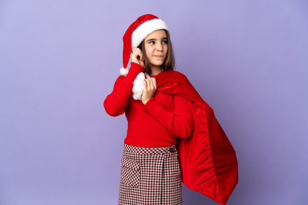 Menina com chapéu e saco de natal isolada na parede roxa frustrada e cobrindo as orelhas