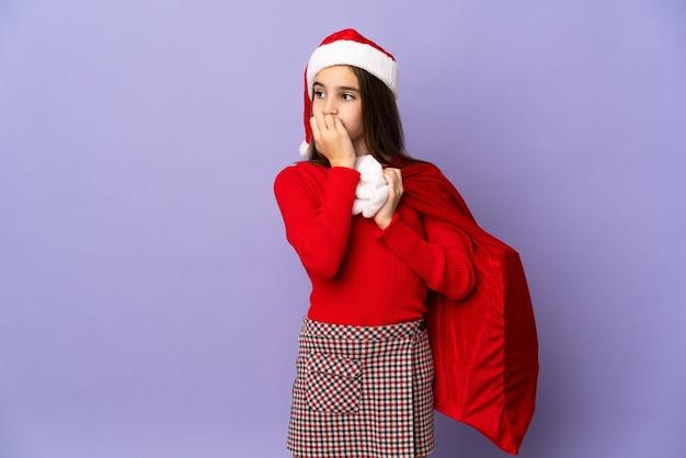 Menina com chapéu e saco de natal isolada no fundo roxo tendo dúvidas