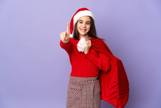 Menina com chapéu e saco de natal isolado na parede roxa, mostrando e levantando um dedo
