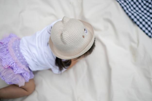 Menina com chapéu está rastejando sobre o pano creme no campo ao ar livre. fotografando de cima.