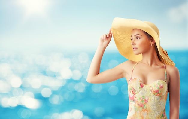 Menina com chapéu na praia com um mar brilhante no fundo